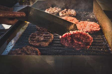 Flaming grill en beef burgers. De kok gooit de Patty op de grill met een metalen spatel Stockfoto