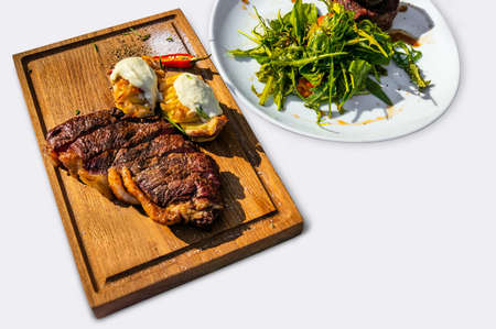 flesh eating animal: Grilled T-Bone Steak on cutting board on dark wooden on a white isolated background