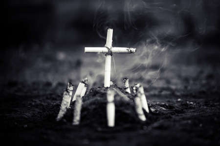 A cemetery with a grave made of cigarettes. Death by harm from nicotine or tobacco smoke from cigarettes. Cigarette kills. black and white grim photo.