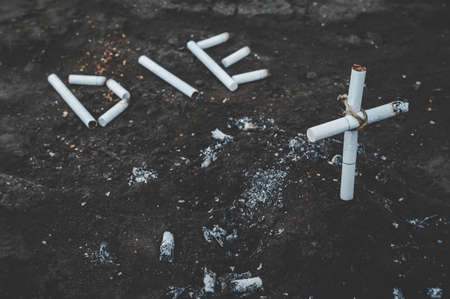 inscription die on the ground lined with cigarettes. tomb of cigarettes and cigarettes with tobacco smoke. Anti-Smoking concept. The dangers of nicotine to health. dark toned photos. Stock Photo