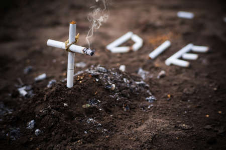 a cross from butts. Smoking kills. word die laid out the cigarettes on the ground next to the grave. the concept of anti-Smoking. Stock Photo