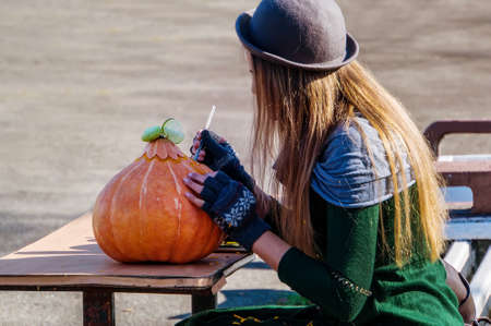 young girl making halloween pumpkin. pre-holiday care on the eve of all saints Day. The female in the hat, at a table on the street carves their pumpkin decorative figure of Jackolantern.