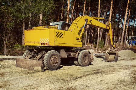 The modern excavator performs excavation work on the construction site. Yellow excavator on wheels.
