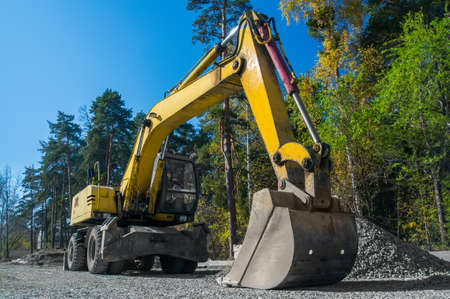 Road repair, asphalt laying. Yellow wheeled excavator Stockfoto