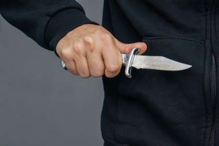 Closeup of a young man hand, holding a knife, about to attack, guy pulled out a knife and threatens. Robbery. mafia.