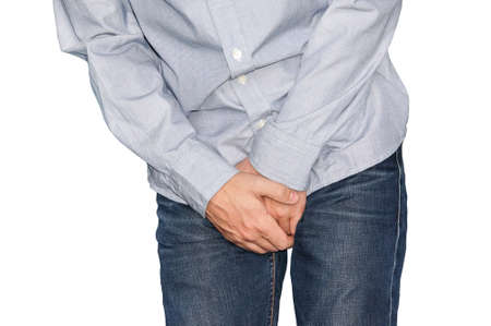 Close up of a man with hands holding his crotch, isolated in white. Urinary incontinence. Disease for men. Men's health.