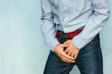 ジーンズと青の背景に彼の股間に手を繋いでいる青いシャツの男。失禁。男性の病気。男性の健康。脚の付け根の打撃からの痛み。 写真素材