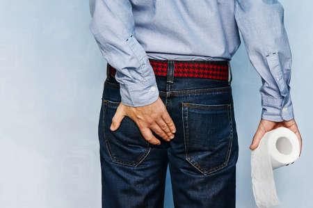 Man die toiletpapierrol houdt en zijn kont op blauwe achtergrond houdt. Diarree concept.