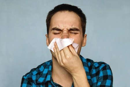 その男の鼻は鼻水だ。風邪を持っている人はハンカチにくしゃみをする。鼻から鼻水が出てくる。 写真素材