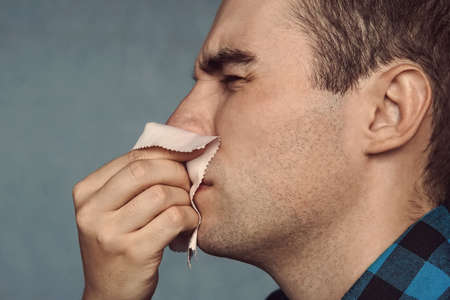 the man has a runny nose. A young guy sneezes in a pink scarf on a blue background. Colds in the fall. Snot coming out of nose.