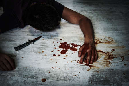 decedent: the body of a young man lying on the floor in a puddle of blood next to the murder weapon, a small folding knife.