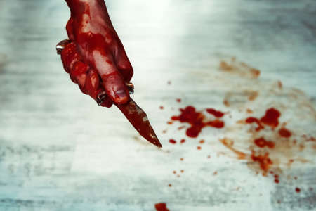carnage: Male hand with bloody knife against the white floor with puddles of blood. Stabbing. Kill with a knife. Stock Photo