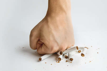 Men hand crushed some cigarettes, No Smoking, Quitting smoking and healthy lifestyle. Guy breaks a cigarette with fingers on white background. The harm of Smoking. To quit Smoking.