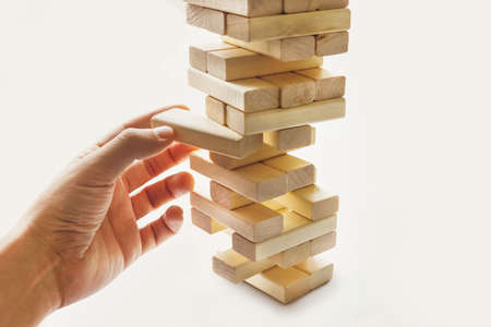 The tower from wooden blocks and man's hand take one block. The game of dice on white background..