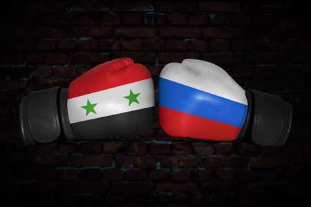 A boxing match. Confrontation between the Syria and Russia. Syrian and Russian national flags on Boxing gloves. Sports competition between the two countries. Concept of the foreign policy conflict.