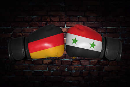 A boxing match. Confrontation between the Germany and Syria. Syrian and German national flags on Boxing gloves. Sports competition between the two countries. Concept of the foreign policy conflict. Archivio Fotografico