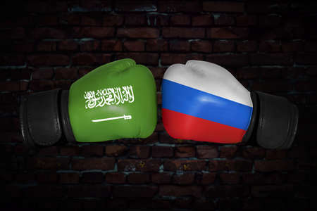 A boxing match. Confrontation between the Saudi Arabia and Russia. Russian and Saudi Arabian national flags on Boxing gloves. Sports competition between the two countries. foreign policy conflict. Stock Photo