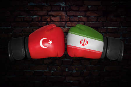 A boxing match. Confrontation between the Turkey and Iran. Turkish and Iranian national flags on Boxing gloves. Sports competition between the two countries. Concept of the foreign policy conflict.