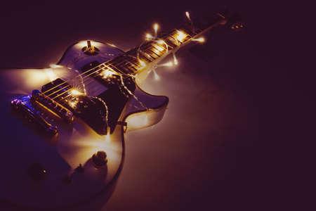 Elektrische gitaar met verlichte garland op donkere achtergrond. Klassieke klassieke gitaarvormen voor kerst of nieuwjaar. Stockfoto
