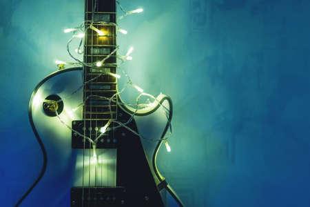 guitarra eléctrica con guirnalda encendida sobre fondo azul oscuro. siluetas de neón de los copos de moda para la navidad o año nuevo .