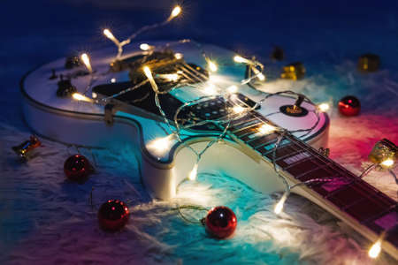 Electric guitar with lighted garland on dark background. Gift guitar classic shapes for Christmas or new year. Archivio Fotografico