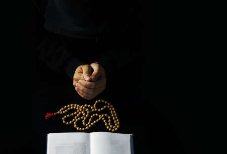 Hands of young priest with holy bible and wood sandalwood rosary