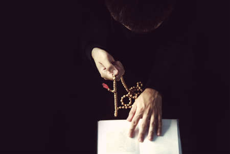 The priest reads a prayer from the book holding a rosary. The concept of religion. Stock Photo