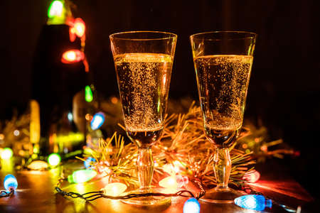 Two Glasses with champagne and bottle on a wooden table decorated with Christmas accessories to celebrate the new year and Christmas. Romantic evening. The glow from the garlands. Valentines Day