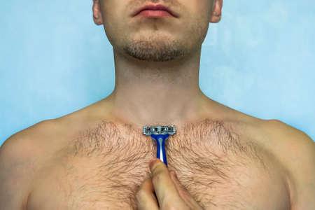 かみそりで胸を剃る男、体のクローズアップ。