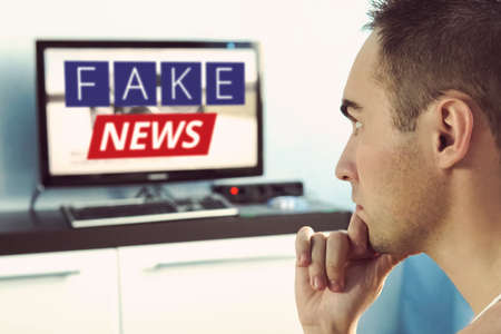 Truth misrepresented in the news on a modern TV. A fake news report. Zombie TV. Deception of viewers. Corrupt journalism. False sites. Agitation and propaganda on the screen. in front of the TV.