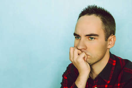 A young man holds her chin with her hand. A pensive pose. Portrait of young man thinking