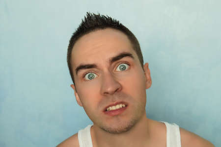 Portrait of young man with scared expression on a blue background. surprised eyes. Surprised emotion on human face. blue-eyed handsome guy.