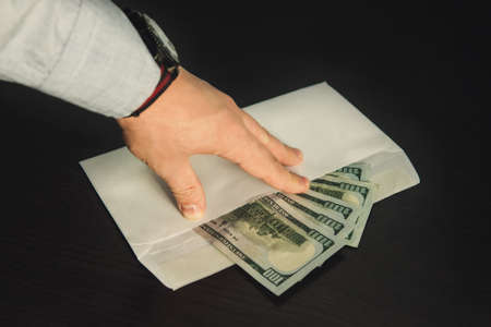 Male hand holding its fingers on white envelope full of American Dollars, USD, US Dollars, on the wooden table as a symbol of illegal cash transfer or bribery, black market or gray economy, Stock Photo