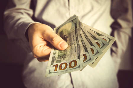 man in a suit holding fan of dollar banknotes. A businessman holds out a bribe of 500 dollars 스톡 콘텐츠