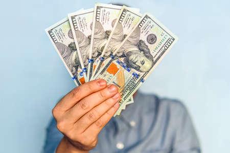 手にドル。青いシャツを着たビジネスマンが500ドルを持っている。金のファン