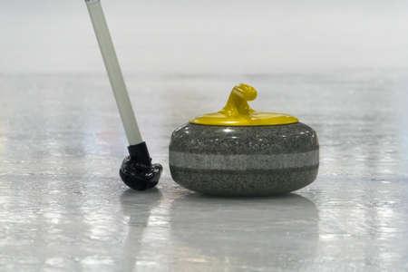 カーリング。氷の上のブラシと黄色のカーリング石
