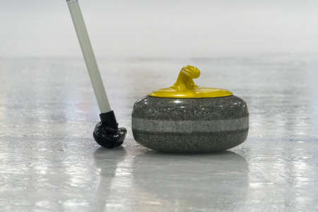 Curling. Brush and yellow Curling stone on the ice