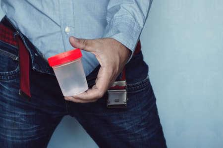 Main tenant un récipient en plastique. l'homme est venu pour être testé dans un pot. Banque d'images - 91132058