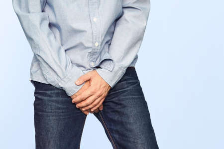 Close up of a man with hands holding his crotch on a light blue background. Urinary incontinence. Men's health. The pain from the blow in groin. Standard-Bild