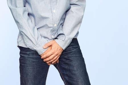 Schließen Sie oben von einem Mann mit den Händen, die seine Gabelung auf einem hellblauen Hintergrund halten. Harninkontinenz. Männer Gesundheit. Der Schmerz vom Schlag in der Leistengegend.