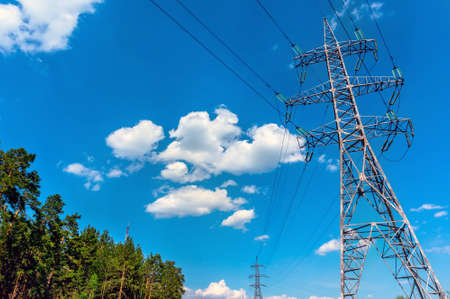 High-voltage lines against the blue sky, green pine forest. electricity Stock Photo