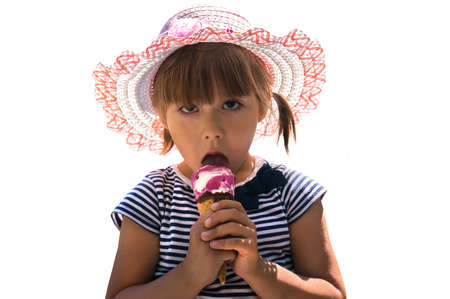 Isolated shot of cute little girl with brown eyes and dark brown hair, wearing pink hat and striped dress, holding fruit an ice cream cone. Portrait of Caucasian child licking popsicle and looking Stockfoto