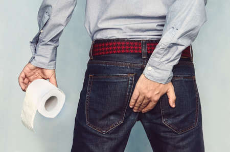 Man suffers from diarrhea holds toilet paper roll. The guy is holding the of himself trying to hold back the urge