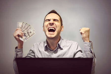man is happy in front of the computer to hold 500 dollars. Winning in an online casino. Profit from online stock trading. Easy money. Earnings on the Internet. Stock Photo