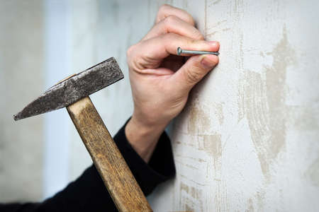Close up on a hand hammering a nail on a wall with mural Wallpaper. to frame the picture on the wall