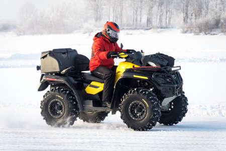 Hombre conduciendo una moto quad en el campo de invierno. Conductor de la moto Quad en traje rojo en amarillo Quad bike closeup. Invierno extremo de entretenimiento