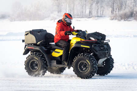 man driving a quad bike in the winter field. driver of the Quad bike in red outfit on yellow Quad bike closeup. Winter extreme entertainment