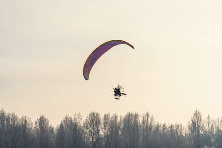 Fly up to the sky. Paraglider in the sky with skis above the trees.