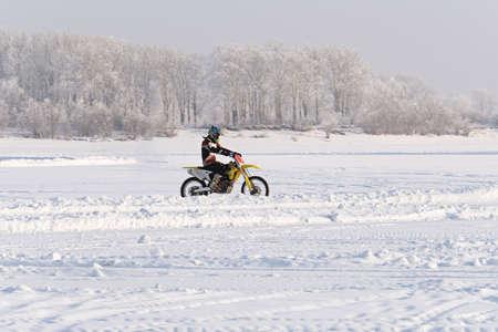 Motorfiets op een winterweg in het veld in de sneeuw op de achtergrond van besneeuwde bomen. Winter extreem leuk. Motorrijden in de winter. extreem plezier in de winter op een motor