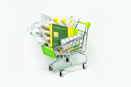 credit card and pill in the shopping cart on white isolated background. Concept of purchasing drugs in pharmacy. increasingly expensive drugs. Stock Photo